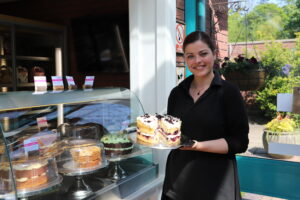Member of staff from Walled Garden Cafe holding a cake